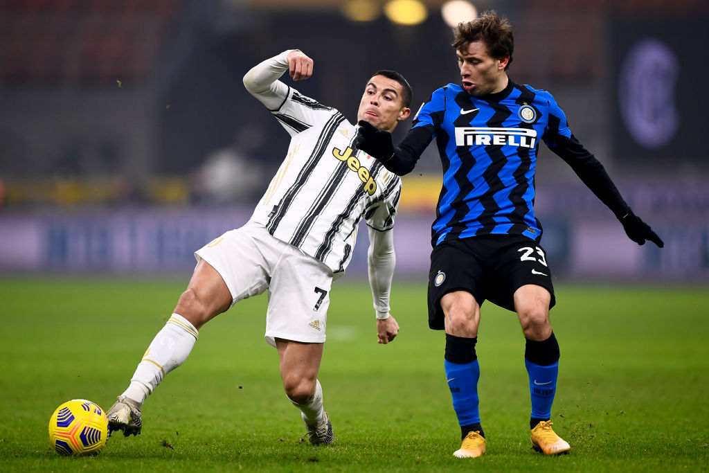 Cristiano Ronaldo (L) of Juventus FC is challenged by Nicolo...